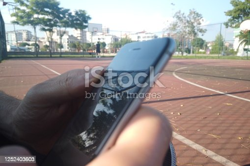 man holding smartphone at basketball court
