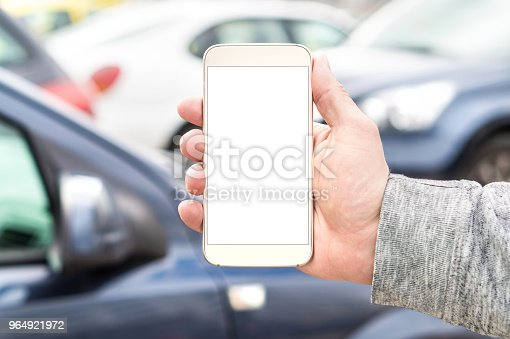 istock Man holding smartphone with empty blank white screen. Many cars or traffic in background. Mobile phone in hand. Template for navigation, parking or ride share app. 964921972