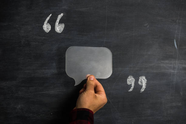 man holding speech bubble between quotation marks on blackboard - testimonial stock photos and pictures