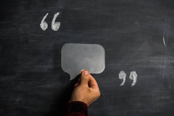 Homme tenant la bulle de dialogue entre guillemets sur tableau noir - Photo