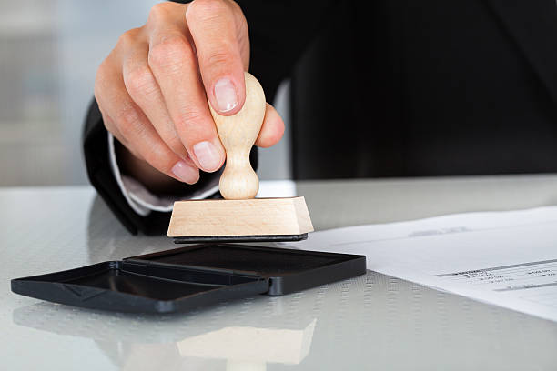 man holding stamp over ink pad to stamp a piece of paper - stamper stock photos and pictures