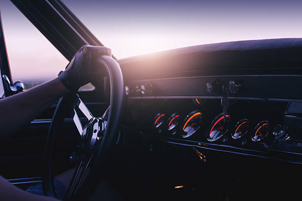 man holding steering wheel inside car at sunset - sports glove stock photos and pictures