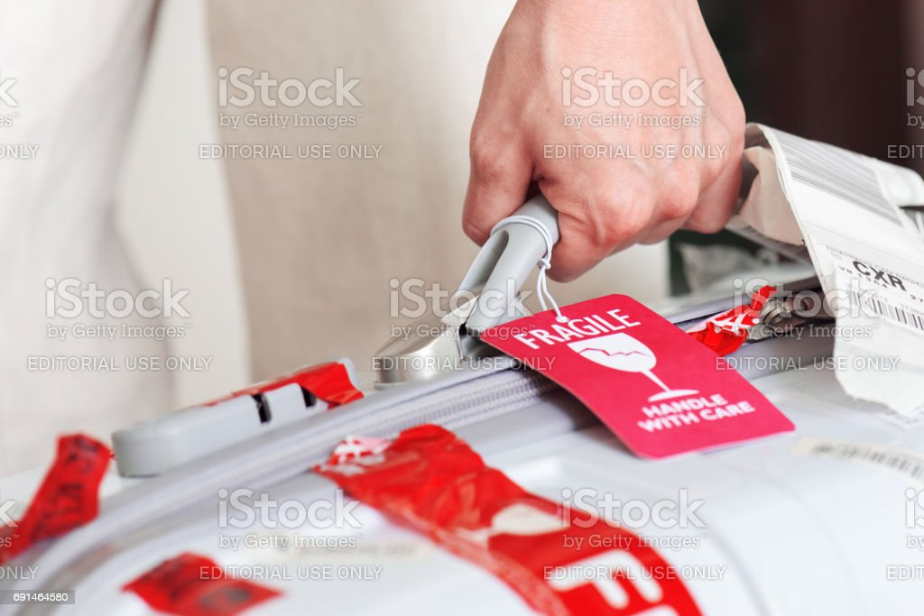Man holding suitcase with luggage tag in hand at airport stock photo