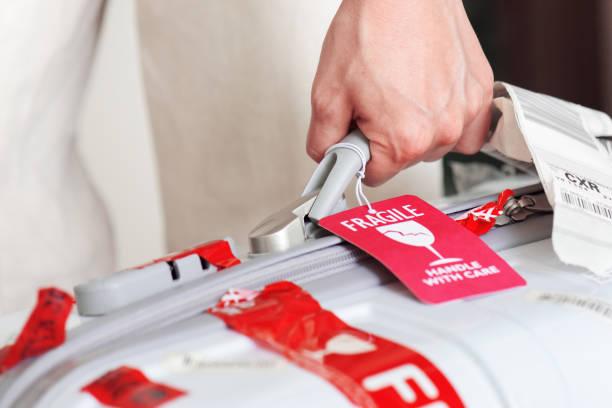 mann hält mit gepäckanhänger koffer in der hand am flughafen - gepäck verpackung stock-fotos und bilder