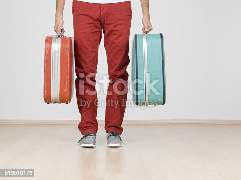 Man holding vintage suitcases, ready to leave home, low section. Copy space to the right