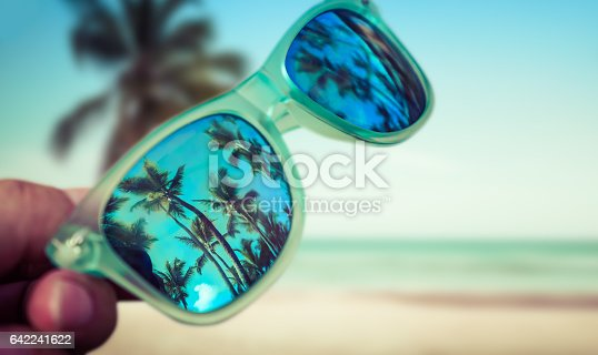 istock Man holding sunglasses in hand at beach 642241622