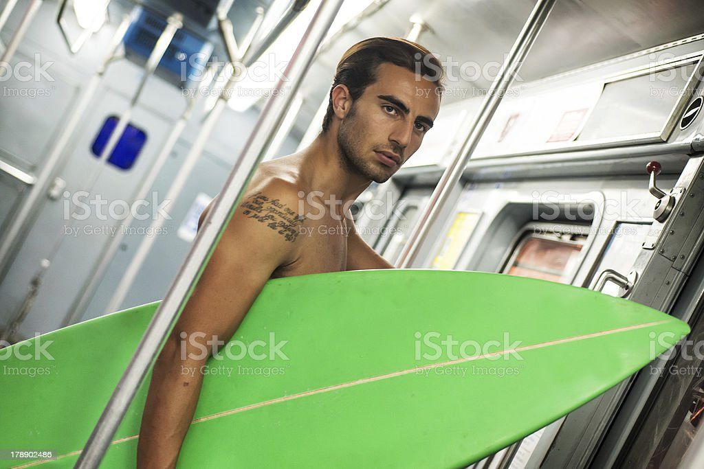 man holding surfboard in subway royalty-free stock photo