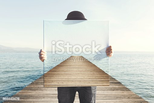 istock Man holding surreal painting of a boardwalk 865443476