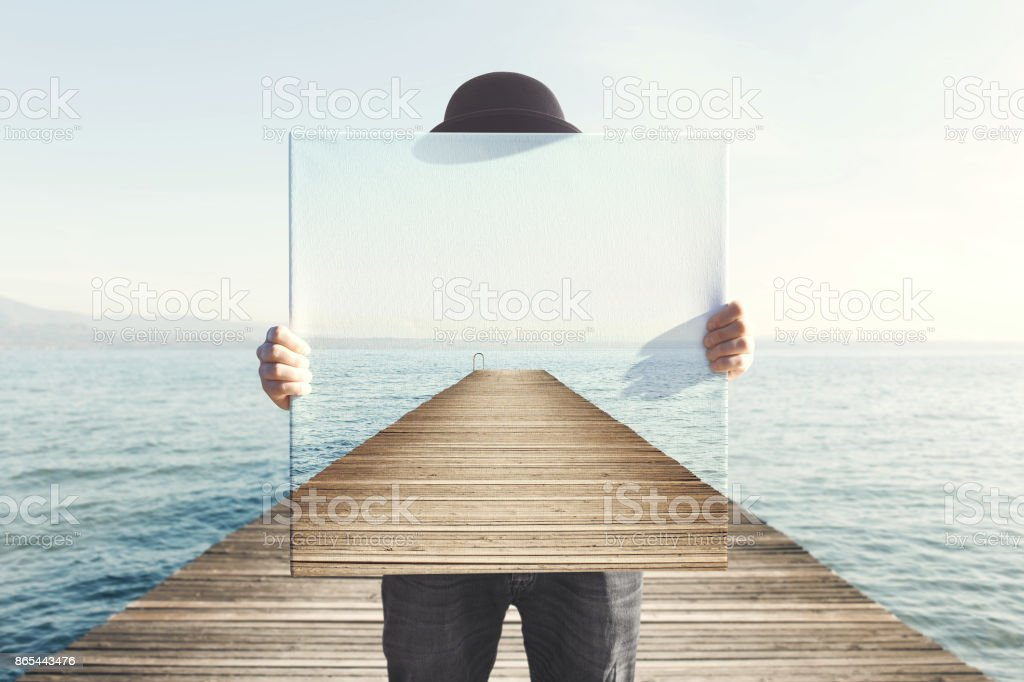 Man holding surreal painting of a boardwalk stock photo
