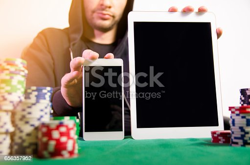 istock Man holding tablet and smartphone, poker apps 656357952