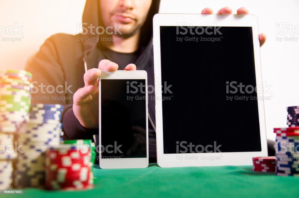 Man holding tablet and smartphone, poker apps stock photo