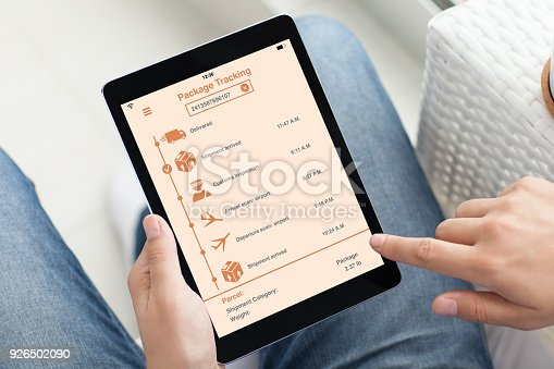 istock man holding tablet computer with app tracking delivery package 926502090