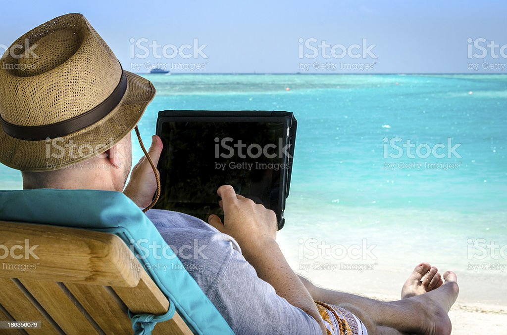 Mann hält tablet im Urlaub am Strand – Foto