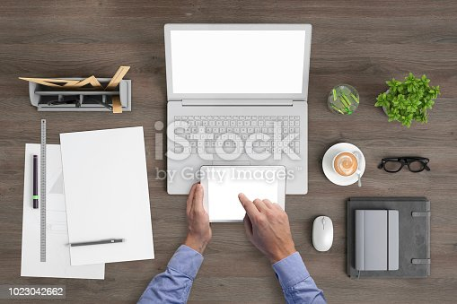 994878714 istock photo Man holding tablet knolling overhead view 1023042662