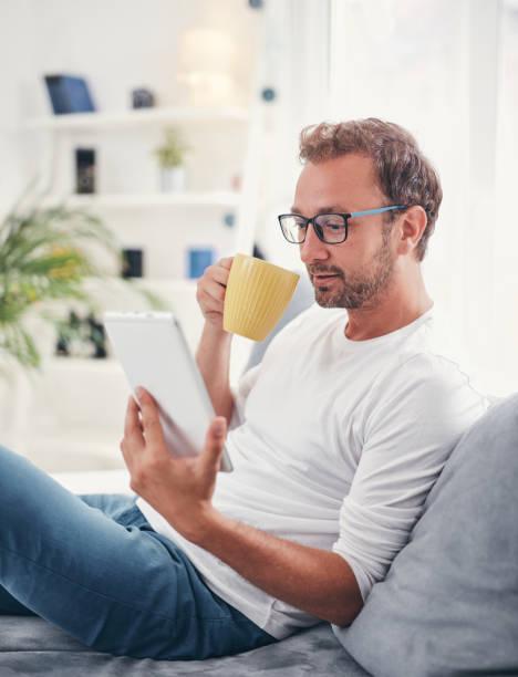 Mann hält Tablet, Surfen online und Kaffee trinken. – Foto