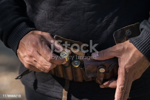 Man holding Tape with cartridges for hunting rifle