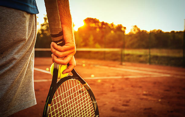 man holding tennis racket - tennis stock photos and pictures