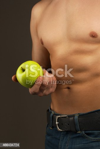 502992735 istock photo Man holding the apple. Abdominal muscles and chest. 466434724