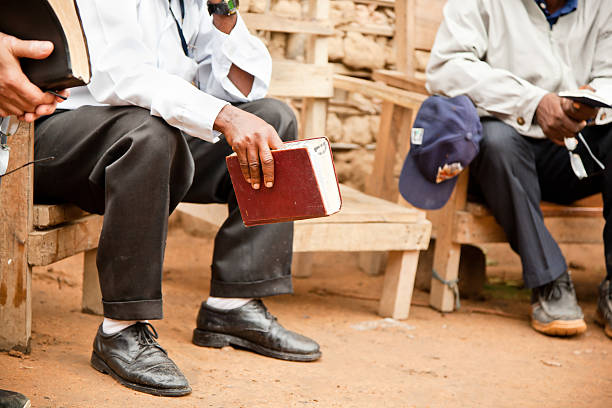 A man holding the bible and sitting on a park bench stock photo