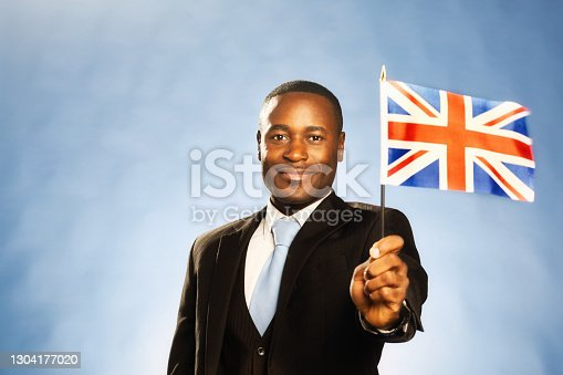 Formally dressed man in a three-piece suit holds a minature version of the UK flag.