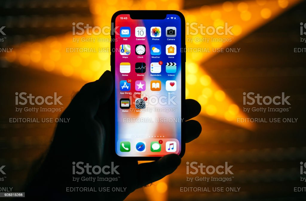 Man holding the new Apple iPhone X 10 Display with yellow star bokeh background stock photo