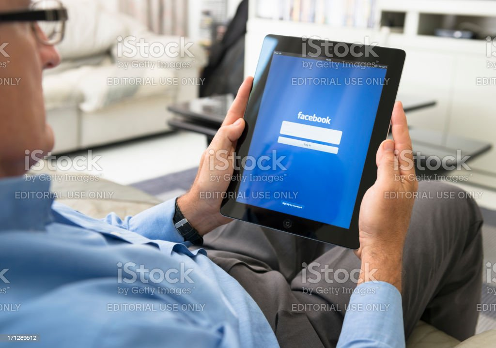 Man holding the new Ipad 3 with Facebook app royalty-free stock photo