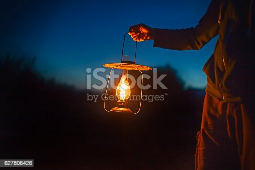 hand holds a large lamp in the dark. ancient lantern with a candle illuminates the way on a night