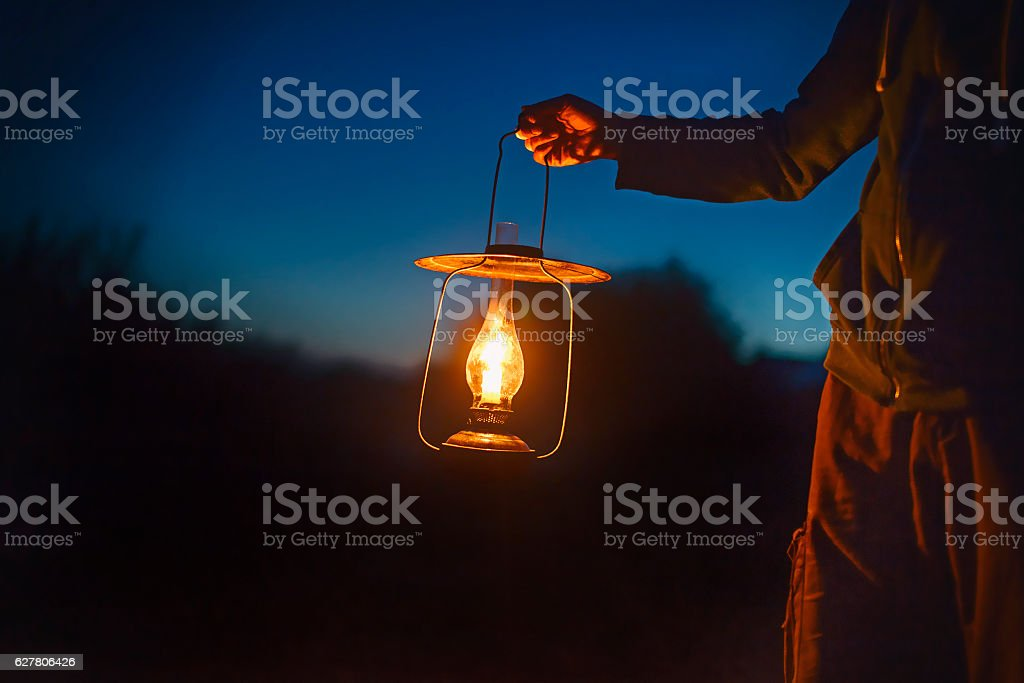 man holding the old lamp with a candle outdoors stock photo