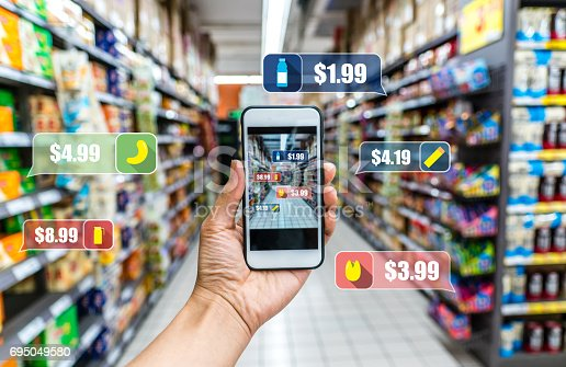 istock man holding the smart phone, using the Augmented Reality buy some food in the supermarket 695049580