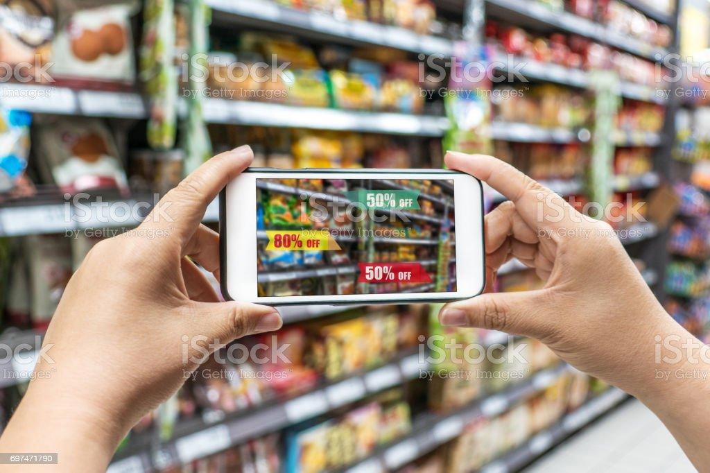 man holding the smart phone, using the Augmented Reality buy some food in the supermarket man holding the smart phone, using the Augmented Reality buy some food in the supermarket Arkansas Stock Photo