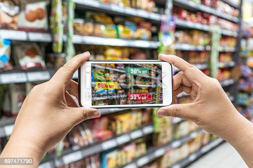 890476604 istock photo man holding the smart phone, using the Augmented Reality buy some food in the supermarket 697471790
