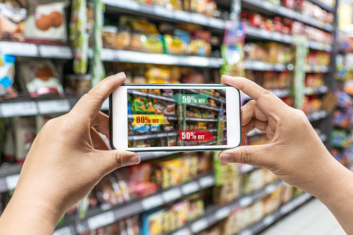 Man Holding The Smart Phone Using The Augmented Reality Buy Some Food In The Supermarket Stock Photo - Download Image Now