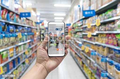 istock man holding the smart phone, using the Augmented Reality buy some food in the supermarket 923245564