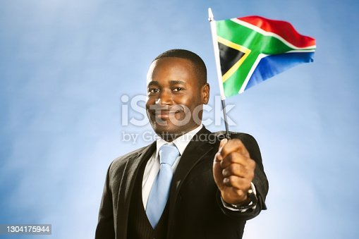 Formally dressed man in a three-piece suit holds a minature version of the South African flag.