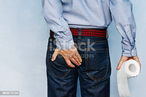 istock Man holding toilet paper roll and holding his butt on blue background. 863573134
