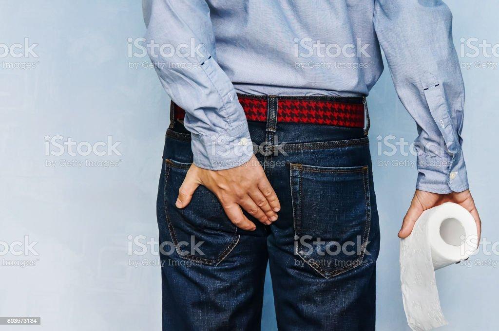 Mann hält Klopapierrolle und hält seinen Hintern auf blauem Hintergrund. – Foto