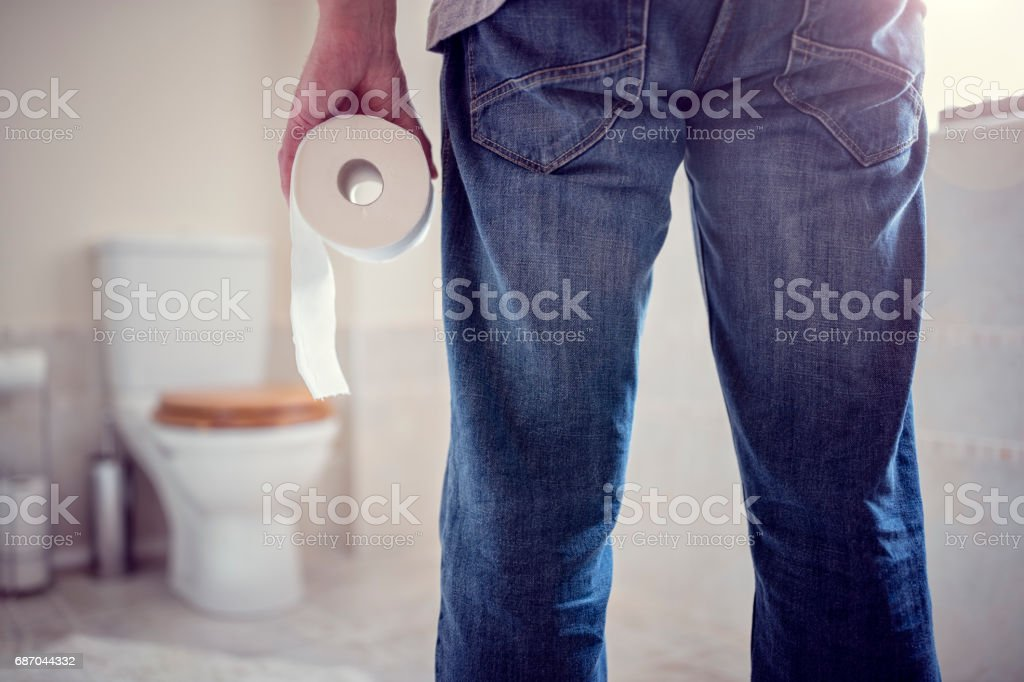 Man holding toilet paper roll in bathroom stock photo