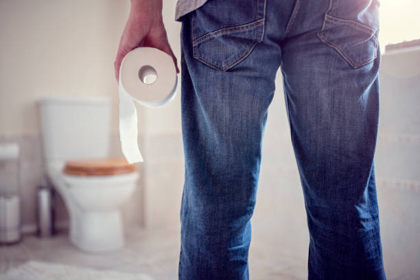 man holding toilet paper roll in bathroom - constipation stock pictures, royalty-free photos & images