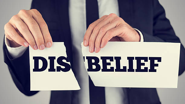 Man holding torn paper with the words Dis-Belief Man holding a torn paper sign in his hands with the words - Dis - Belief - spread over the two halves depicting the concept of opposites - Belief and Disbelief. deem stock pictures, royalty-free photos & images