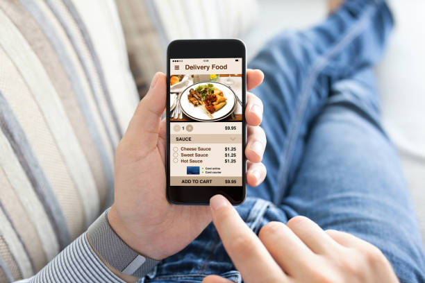 man holding touch phone with app delivery food on screen - food delivery стоковые фото и изображения
