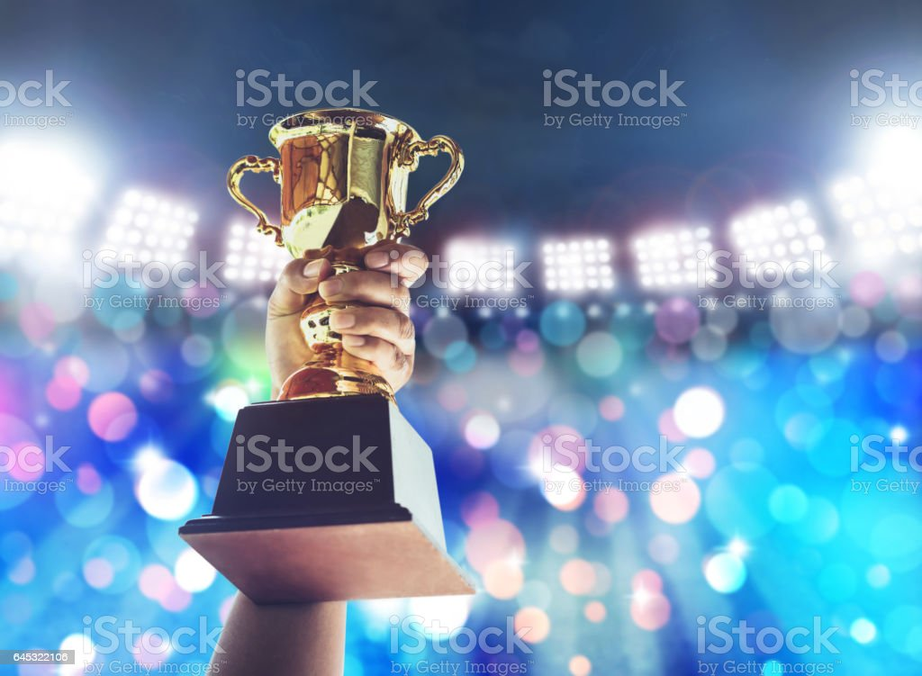 Man holding up a a gold trophy cup,win concept. stock photo