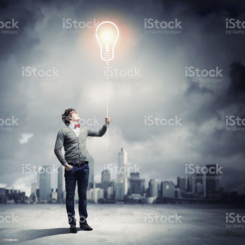 A man holding up an illuminated gigantic light bulb royalty-free stock photo