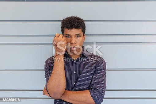istock man holding up forearm with leather wrist band 839368418
