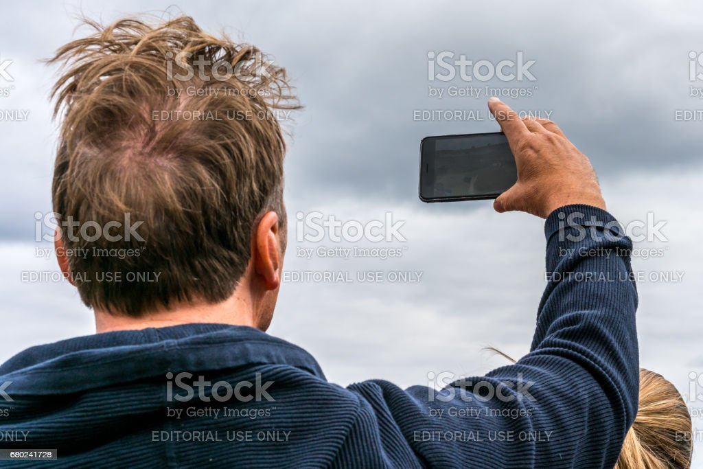 Man holding up mobile phone against cloudy sky. stock photo
