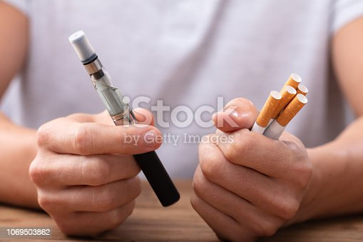 Man Holding Vape And Tobacco Cigarette Over Desk