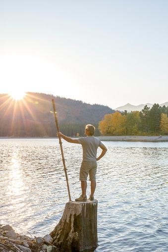 Man holding walking stick stands on stump over lake, sunrise