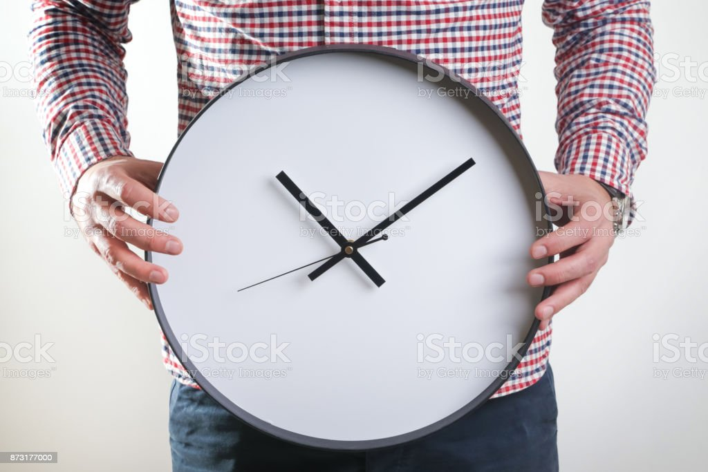 Man holding wall clock stock photo