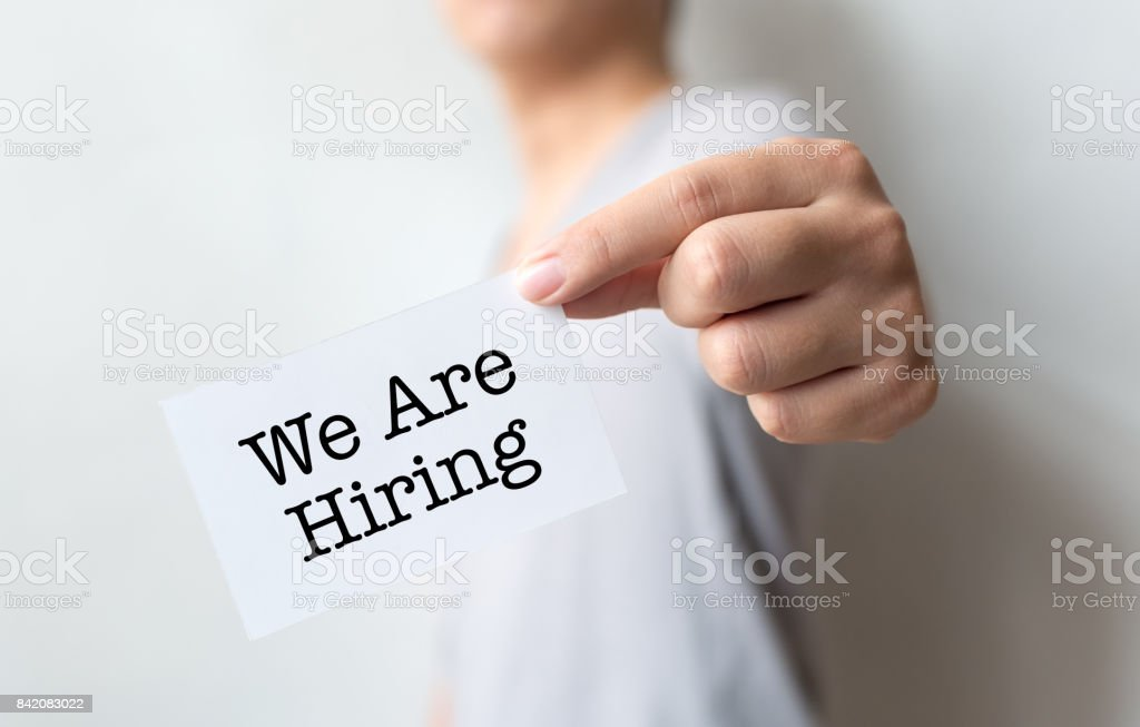 Man holding we are hiring word on paper card, Concept job recruitment and human resource stock photo