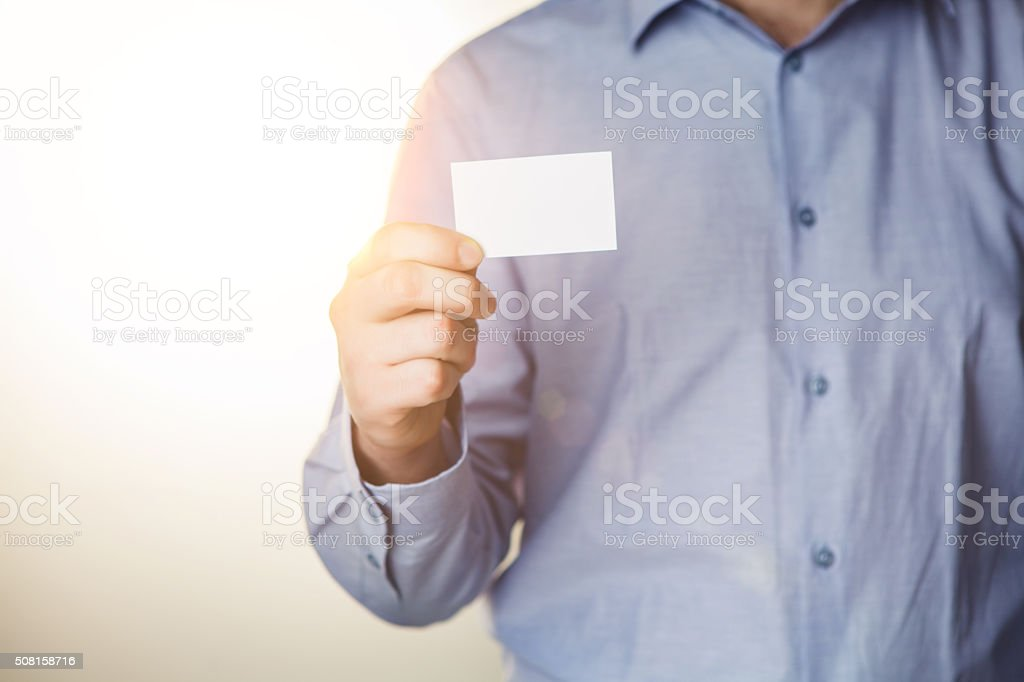 Man holding white business card stock photo