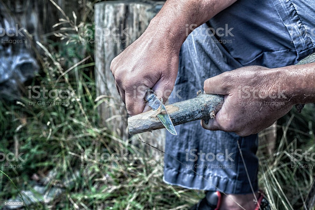 Man Holding Whittling Knife Carving Wooden Stick stock photo